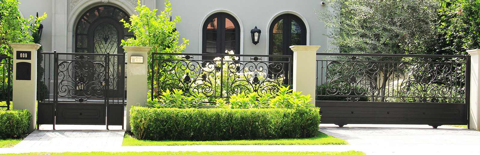 Black wrought iron and sheet metal sliding gate and hinged pedestrian gate