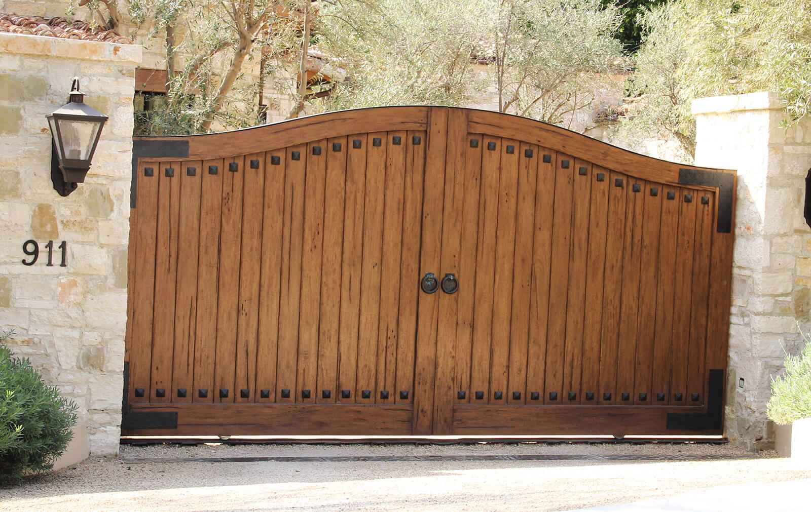 Custom finished exotic hardwood single sliding gate with hand hammered cast iron accents