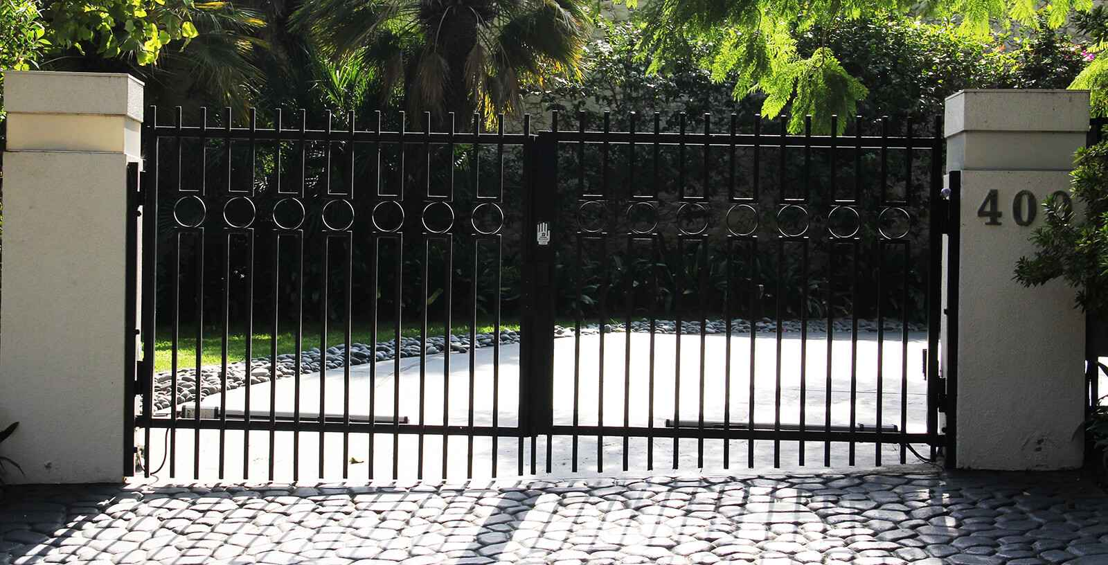 Contemporary steel and glass folding auto gate and hinged pedestrian gate