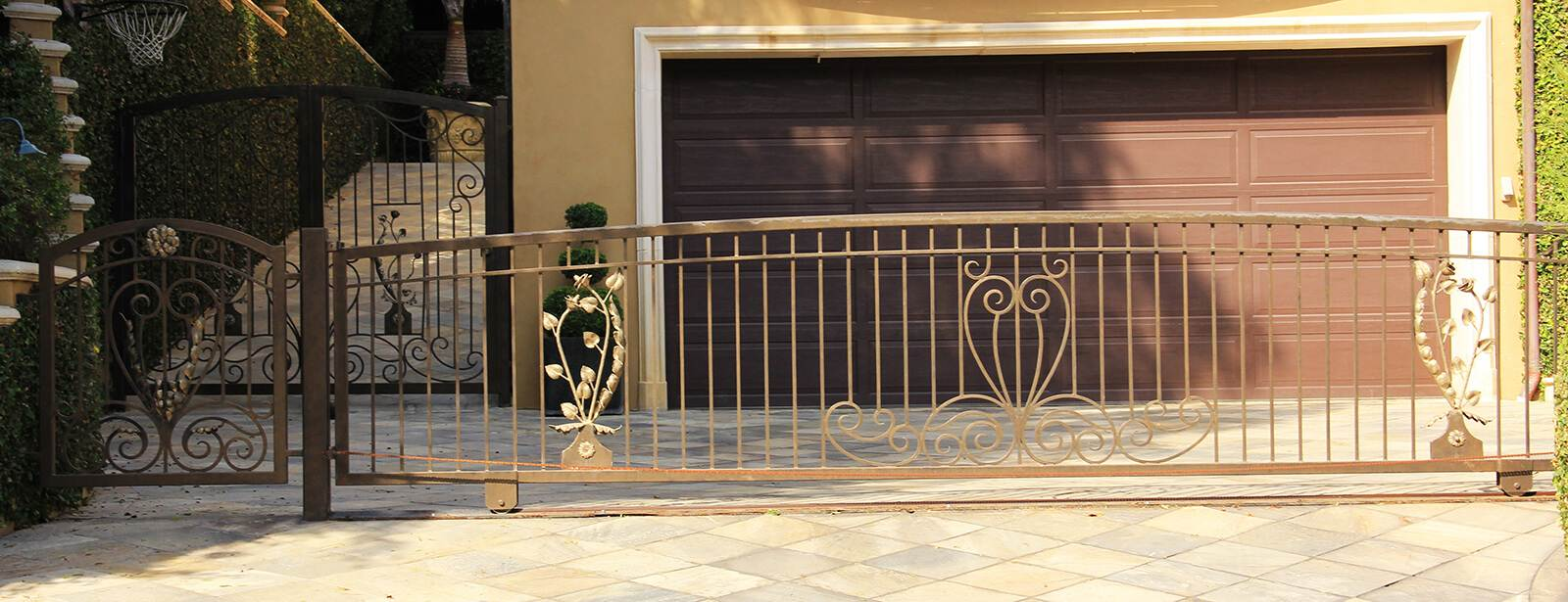 Decorative gold tinted sliding gate and hinged pedestrian gate