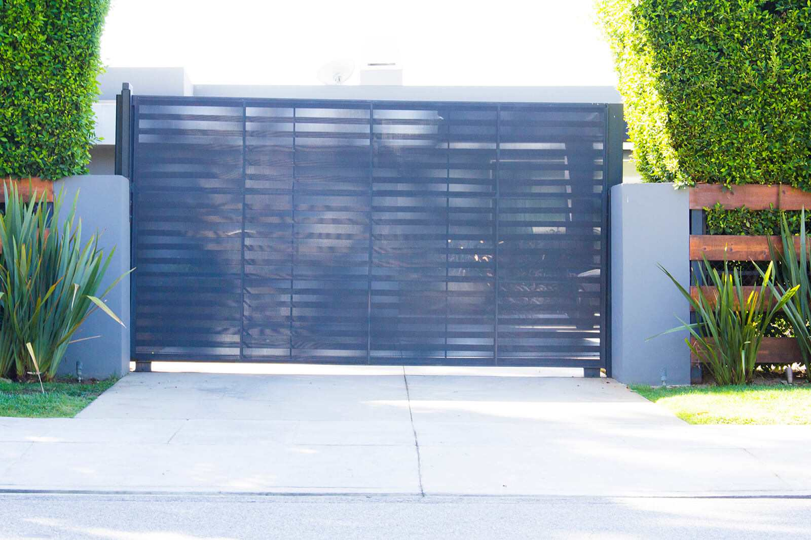 Black steel single slide gate with laser etched privacy screen