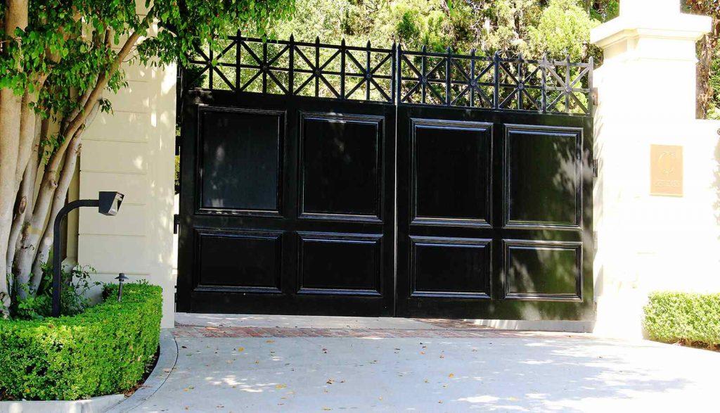 Wood paneled bifold auto entry gate