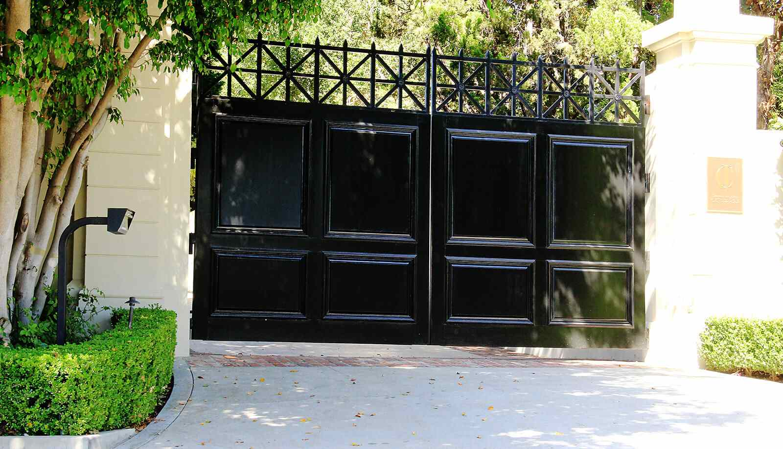 Wood paneled bifold auto entry gate