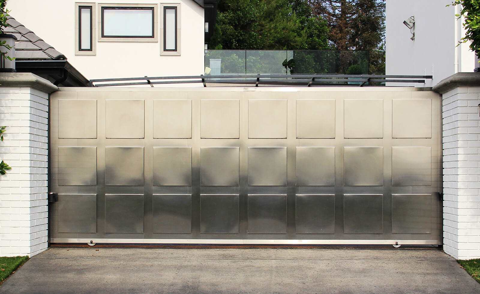 Single slide auto gate in contemporary stainless steel with stainless medallions