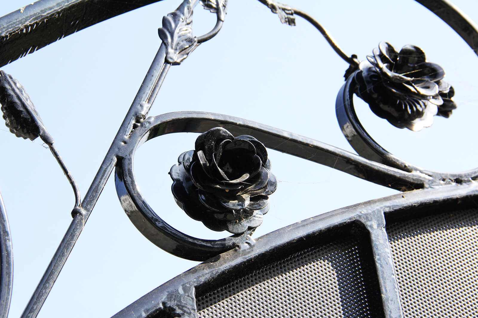 Close up of handmade flower and leaf appliques on wrought iron gate
