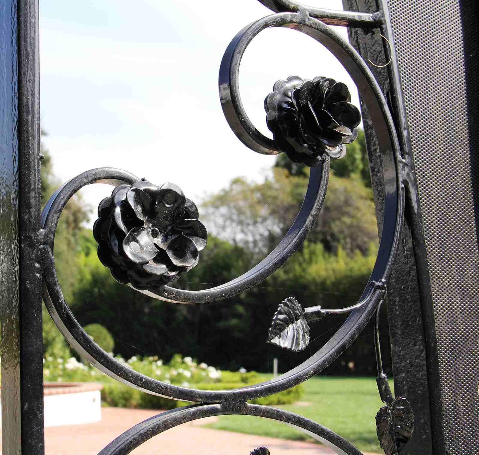 Side close up of handmade flower and leaf appliques on wrought iron gate