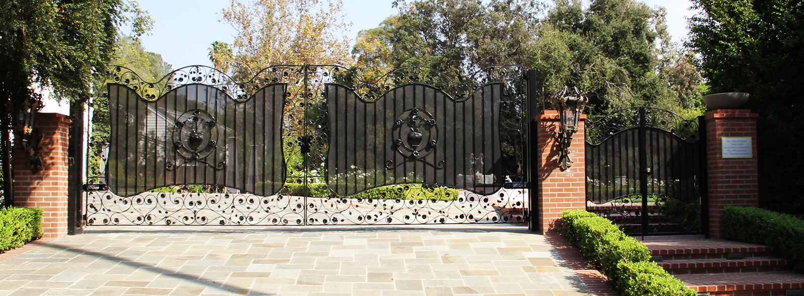 Bifold wrought iron gate with steel mesh and decorated with handmade flower and leaf appliques