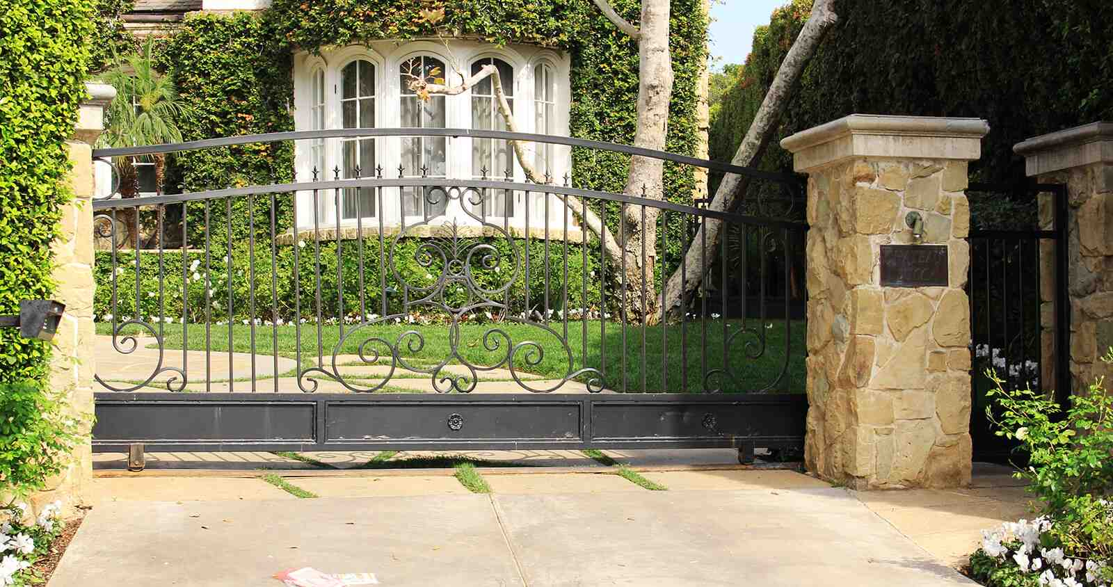 Traditional wrought iron single slide auto gate and single fold pedestrian gate with tropical gold flower and leaf accents