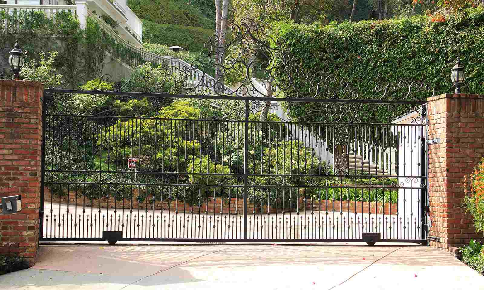 Wrought iron sliding gate with vertical spindles and scrolled top
