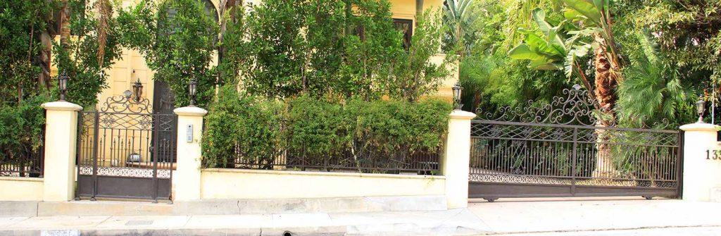Custom hillside wrought iron sliding gate and hinged pedestrian gate
